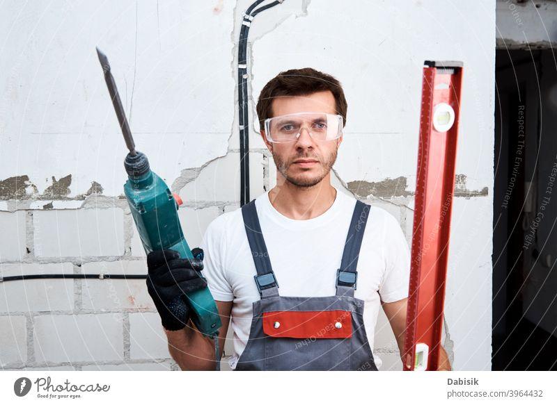 Arbeiter Mann mit Bohrhammer und Gebäude Ebene auf der Baustelle Renovierung bohren Heimwerker Reparatur Schutz Bauherr Konstruktion männlich Wand Instrument