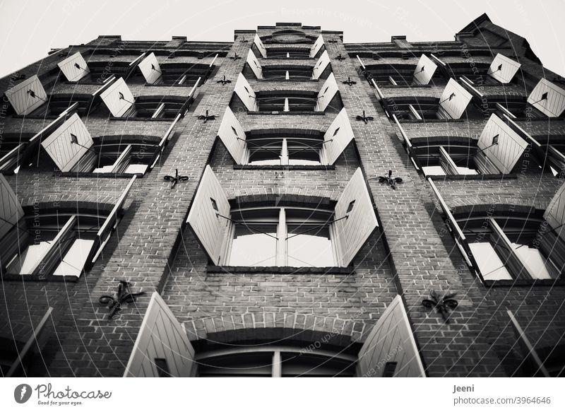 Giebel eines alten Backsteinhauses |die Fensterläden sind symmetrisch geöffnet | schwarzweiß Giebelseite Fassade Backsteinwand Fensterladen fensterläden