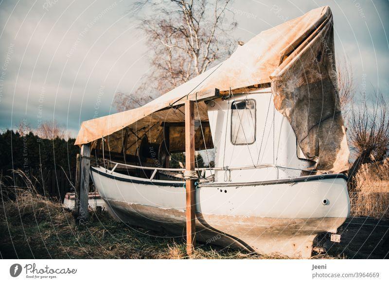 Ein für den Winter an Land festgemachtes Fischerboot in einem kleinen Fischereihafen Fischerdorf Boot abgedeckt an Land bringen trockengelegt trocken gelegt