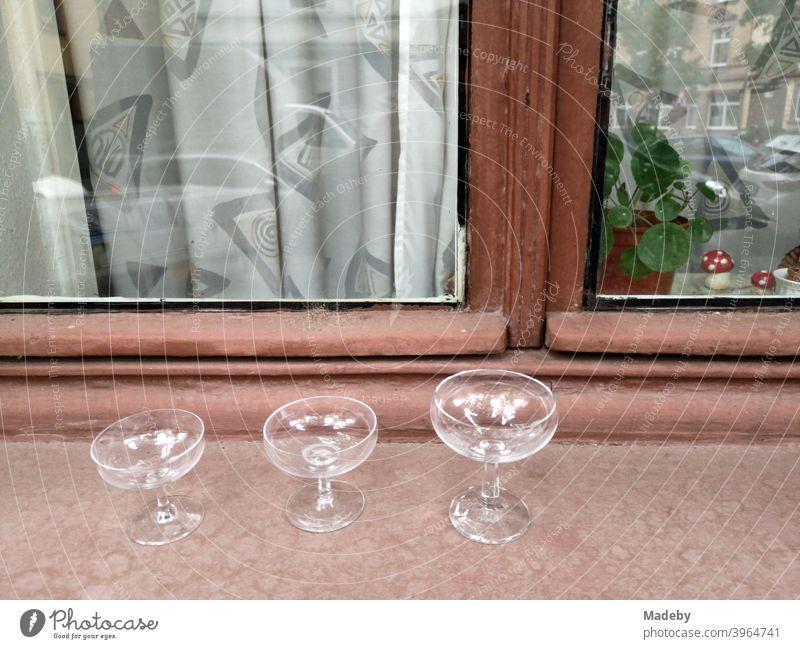 Leere Gläser und Likörschalen auf der Fensterbank eines Altbau mit Holzfenster und Gardine im Nordend von Frankfurt am Main in Hessen Likörglas Glas Stillleben