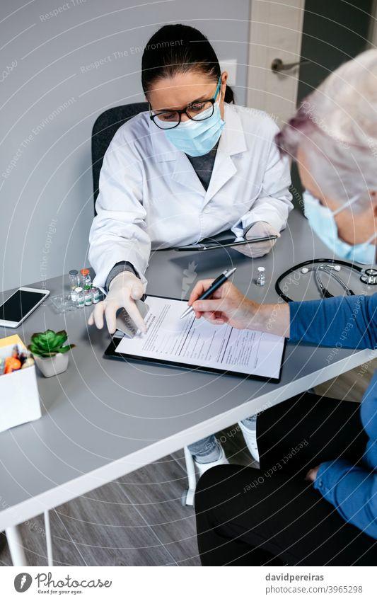 Ärztin erklärt ihrem Patienten die Einverständniserklärung zur Coronavirus-Impfung Coronavirus-Impfstoff Arzt zu erklären. Klärung von Zweifeln Hilfe