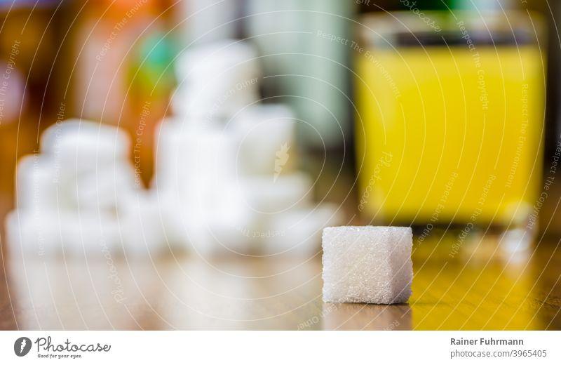 Ein Stück Würfelzucker liegt auf einem Tisch. Ein Glas mit Saft und viele Zuckerstücke sind im unscharfen Hintergrund. Kohlenhydrate süß Lebensmittel Ernährung