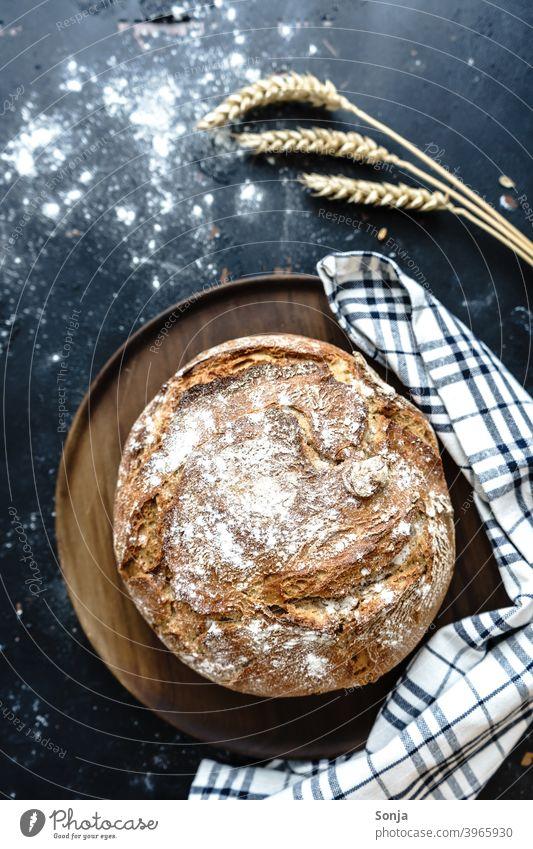 Ein knuspriger Brotlaib auf einem Holzbrett gebacken rustikal Kruste frisch Ernährung selbstgemacht organisch Frühstück Weizenähre geschirrtuch kariert