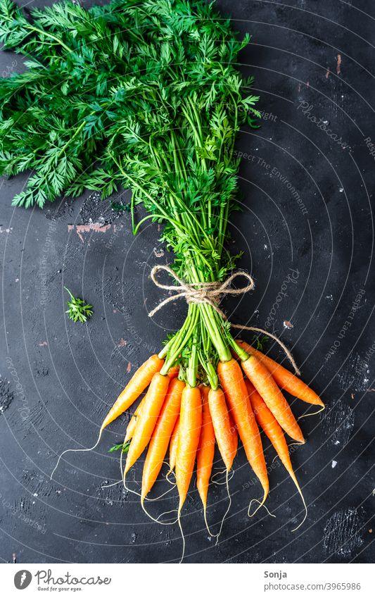 Ein Bund Karotten auf einem schwarzen Hintergrund grünzeug Bund 19 orange Gemüse Karotin Vegetarische Ernährung Bioprodukte Lebensmittel Farbfoto Gesundheit