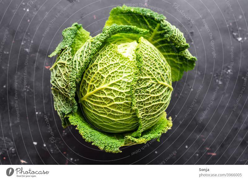 Ein roher Wirsing auf einem schwarzen Hintergrund. Draufsicht Kohl grün Gemüse Lebensmittel Ernährung Vegetarische Ernährung Gesundheit Bioprodukte Farbfoto