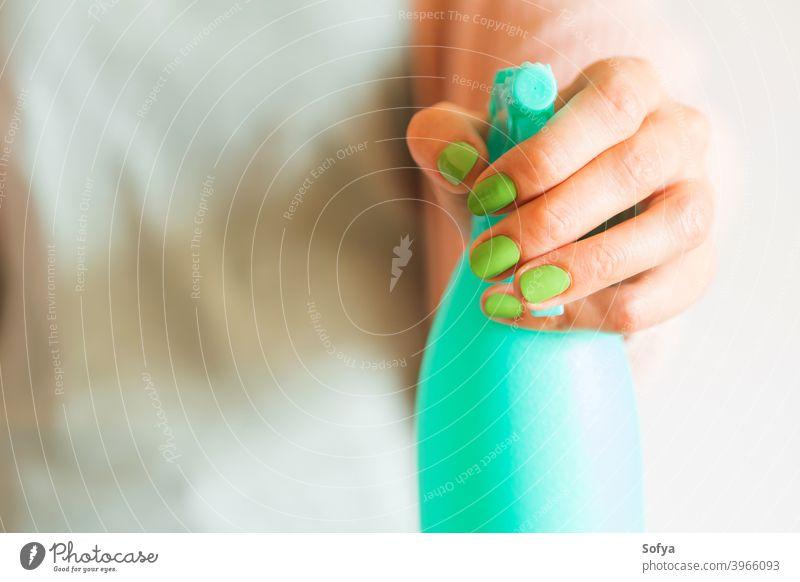 Hand der Frau hält mintgrüne Sprühflasche Flasche Spray Spülmittel Reinigen hausgemacht liquide spritzend rosa Produkt Hintergrund Schönheit Essig Wasser Pflege