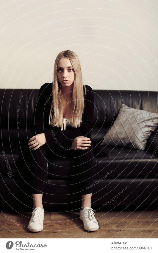 Porträt einer jungen blonden Frau, die auf einer schwarzen Ledercouch sitzt und beobachtet Mädchen schlank langhaarig dunkel Nacht hübsch zierlich wild