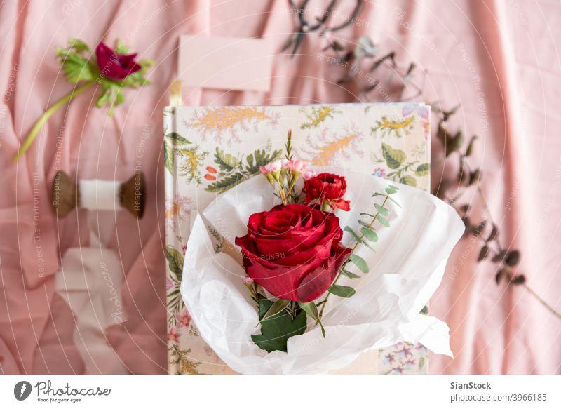 Kleiner Blumenstrauß aus roten Rosen, Ansicht von oben weiß Papier Roséwein Pastell Hintergrund vereinzelt Valentinsgruß Tag rosa grün Frühling geblümt Sommer