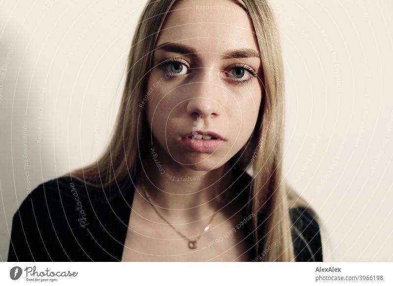 Porträt einer jungen langhaarigen blonden Frau in einem hellen Raum vor einer weißen Wand Mädchen schlank hübsch zierlich wild Lifestyle lange Haare Erwartung