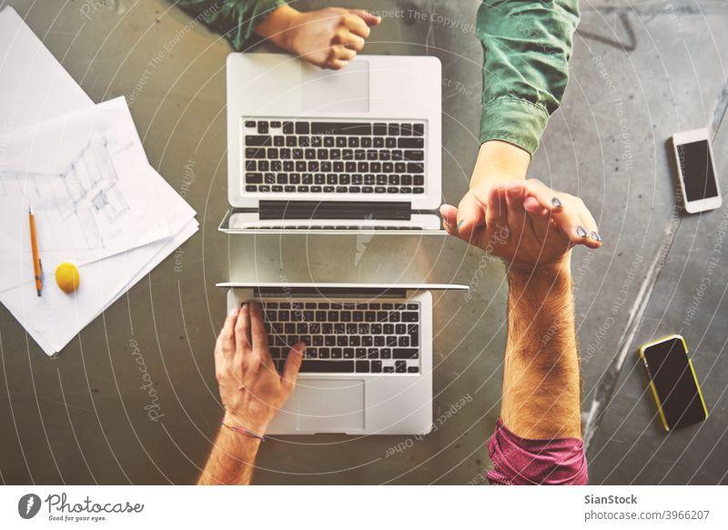 Draufsicht auf Architekten geben High-Five während der Arbeit am Computer im Büro Laptop Business Arbeitsplatz Hände Keyboard Schreibtisch Hand Tisch arbeiten