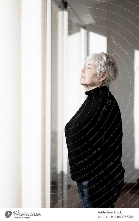 Entspannte Seniorin zu Hause am Fenster Frau Kaukasier älter heimwärts Europäer Lifestyle Porträt Menschen entspannend in den Ruhestand getreten Gelassenheit