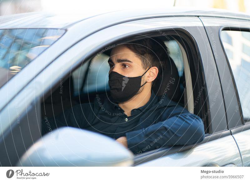 Junger Mann am Steuer seines Autos. Gesicht Mundschutz Laufwerk PKW Sitzen Freizeit Straße reisen Schutzmaske Gesichtsmaske fahren Großstadt Verkehr