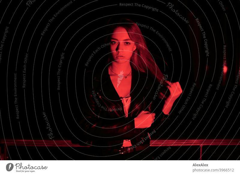 Porträt einer jungen langhaarigen Frau in der Dunkelheit mit rotem Licht junges Fräulein Mädchen schlank blond wehende Haare dunkel nachts Nacht hübsch zierlich