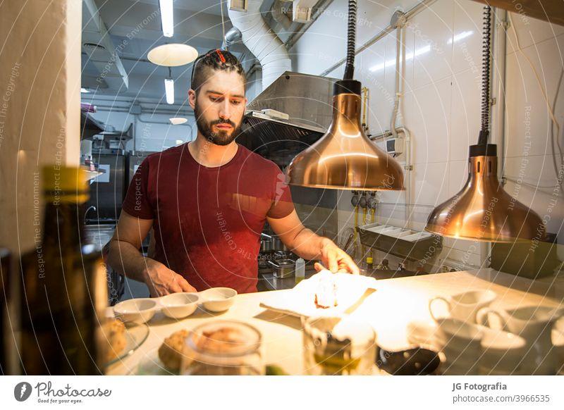 Koch bei der Arbeit in der Küche. Dienst rotes Fleisch Essen und Trinken engagiert jung Beschichtung wirtschaftlich Kochen stylen Catering 2 Küchenchef Ordnung