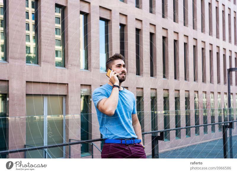 Porträt eines fröhlichen modernen Geschäftsmannes, der am Telefon spricht und lächelt, während er im Freien steht Gebäude Mann sprechend Mobile Großstadt