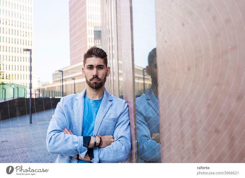 Junger bärtiger Mann mit verschränkten Armen, Model der Mode, im städtischen Hintergrund in lässiger Kleidung cool Stil Porträt Typ 1 photogen stylisch modern