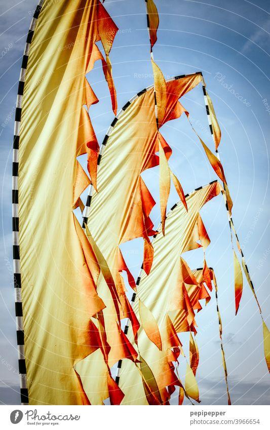 Beachflag Fahnen wie Feuer Wind Fahnenmast flattern wehen Himmel Außenaufnahme Menschenleer Schönes Wetter gelb rot Wolken Blauer Himmel wehende fahnen Flagge