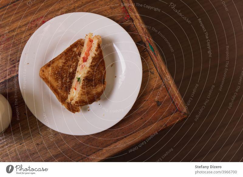 Getoastetes Käsesandwich auf einem weißen Teller, zusammengestellt auf einer Ecke eines Holztisches Belegtes Brot Mittagessen Snack hölzern Tisch felicious