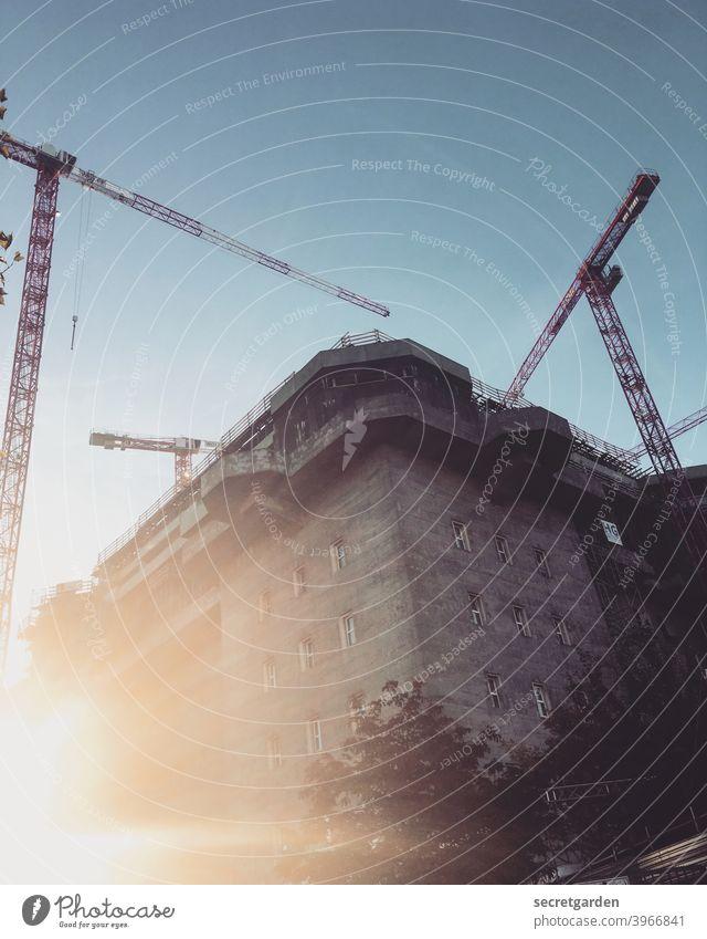 Geblendet vom Kranballett im Sonnenaufgang. Bunker Baustelle Hamburg Sonnenlicht Architektur Außenaufnahme Farbfoto Menschenleer Stadt Bauwerk Beton Gebäude Tag