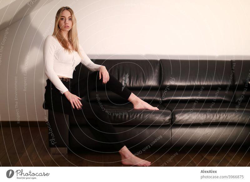 Portrait einer jungen, blonden Frau die barfuß auf einer schwarzen Ledercouch sitzt und schaut Mädchen schlank langhaarig dunkel Porträt Nacht hübsch zierlich