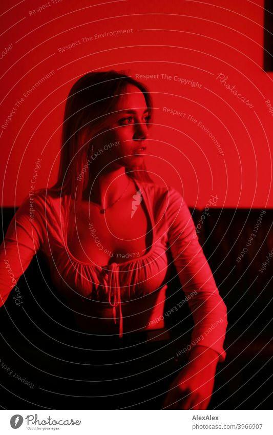 Porträt einer jungen, langhaarigen Frau in der in einem dunklen Raum mit rotem Licht junges Fräulein Mädchen schlank blond dunkel nachts Nacht hübsch zierlich