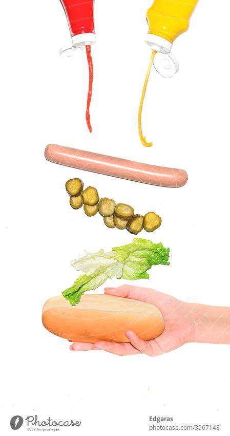 Hot Dog mit verschiedenen Zutaten fliegend halten Hotdog Hot Dog halten Schnappt sich Hot Dog anders vereinzelt Hand Beteiligung Grabbing Ketchup Lebensmittel