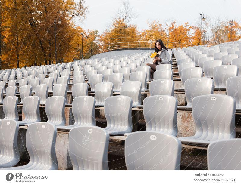 junges Mädchen im grauen Mantel sitzt auf einem Sitz in einem leeren Stadion Frau Sitzen Herbst allein Traurigkeit einsam Kaukasier schön Emotion im Freien