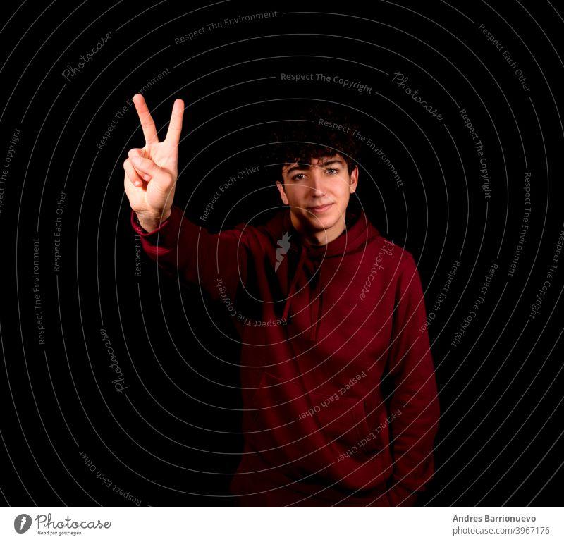 Attraktiver junger Mann macht das Siegessymbol auf einem schwarzen Studio Hintergrund Glück Kaukasier photogen gestikulieren Hemd schön positiv Erwachsener