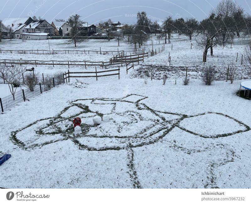 Kind malt im Schnee Formen in Riesen -Format Schnee Kind malt zeichnet Fantasie Form weiß abdrücke im Schnee Winter Freude Spielen Außenaufnahme Lächeln