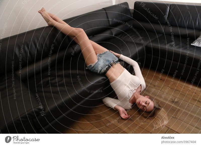 Porträt einer jungen blonden Frau in Hotpants, die barfuß und falschherum auf einer schwarzen Ledercouch liegt Mädchen schlank langhaarig dunkel hübsch zierlich