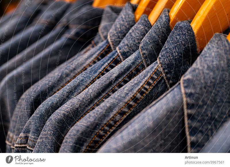 Selektiver Schwerpunkt auf Jacken-Jeans, die im Kleiderladen auf einem Ständer hängen. Denim-Jeans mit Jeans-Muster. Textilindustrie. Jeansmode und Einkaufskonzept. Konzept der Bekleidung. Denim-Jacke im Regal zum Verkauf.