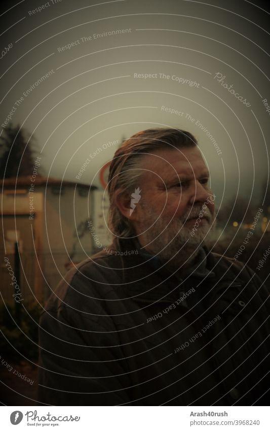 älterer Herr am Abend nachdenklich älterer Mann Porträt Bart Kälte Winter Ändern rentner im Freien spazieren Natur Bewegung Erholung nachdenken freizeit