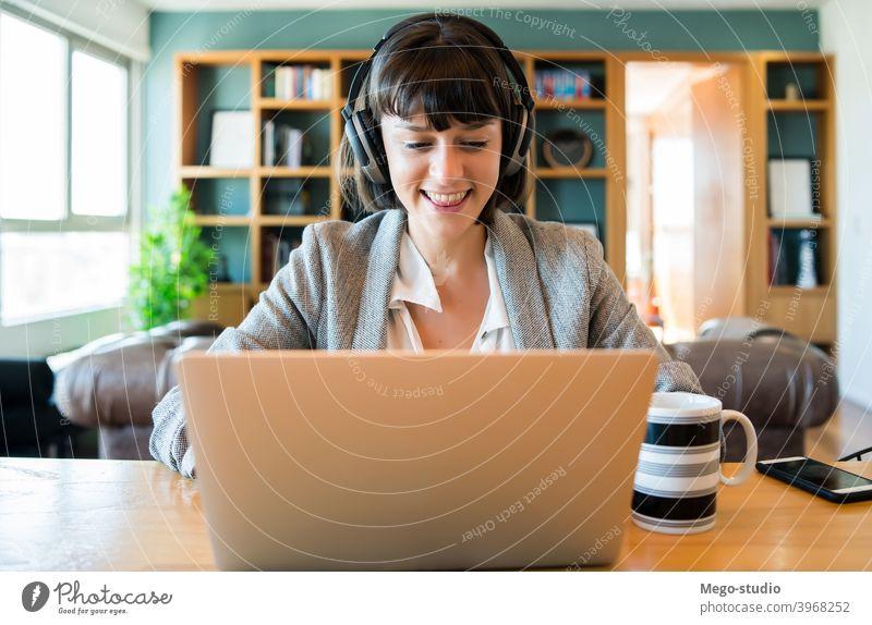 Geschäftsfrau bei Videoanruf von zu Hause aus. Frau heimwärts Büro Anruf Business Arbeit Tagung Technik & Technologie Kopfhörer Laptop online Internet covid-19