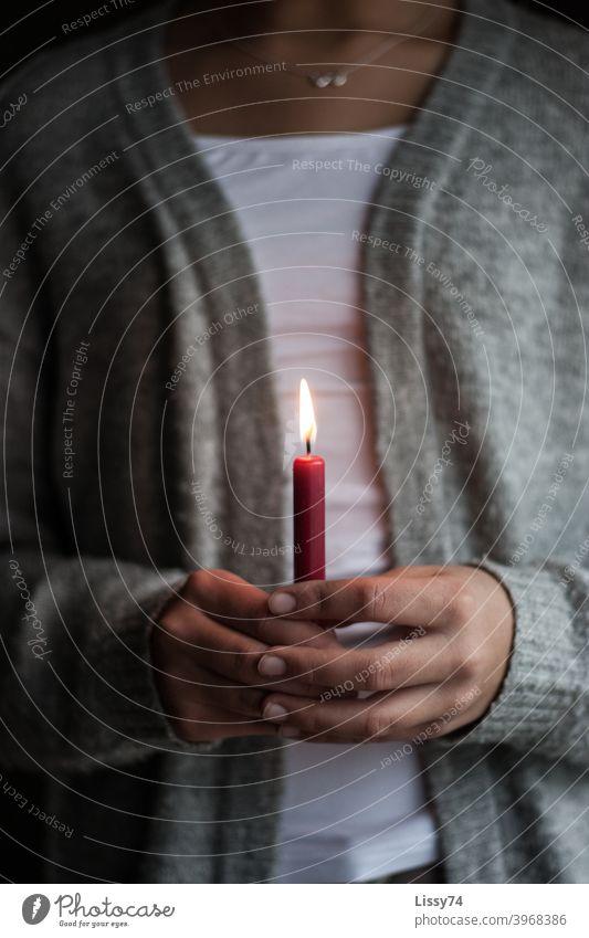 Eine einzelne rote, brennende Kerze gehalten von einem Mädchen Kerzenflamme Hände in den Händen  halten Licht andächtig gemütlich Wärme Advent Weihnachten