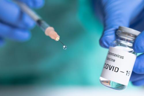 Nahaufnahme der Spritze mit einem Impftropfen. Fokus auf den Tropfen. Coronavirus COVID Korona 19 Virus Behandlung Kur Medikament Einspritzung Schuss Therapie