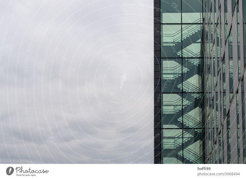 Transparentes Treppenhaus mit wolkigem Himmel - es ist kalt draussen. grün Treppengeländer düster dunkel diffus transparenz Hochhaus Architektur