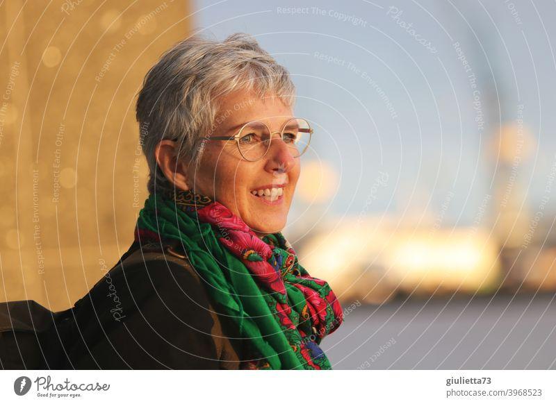 Glückliche, lebensfrohe Frau, stilvoll, junggeblieben, 50+, natürlich schön, schaut lächelnd in die Abendsonne Blick nach vorn Oberkörper Porträt