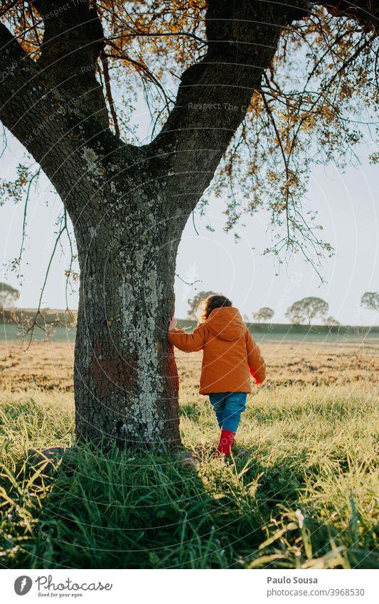 Rückansicht Kind in der Nähe eines Baumes unkenntlich Spielen Mädchen Natur Fröhlichkeit Farbfoto Tag Mensch niedlich Lifestyle Freizeit & Hobby Kleinkind Glück