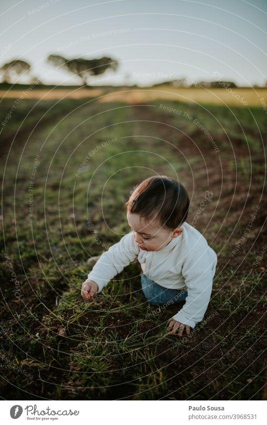 Kleinkind spielt im Freien authentisch Natur Feld Herbst Winter Tag Windstille erkunden Kaukasier Kind Kindheit Familie & Verwandtschaft Freude Spielen