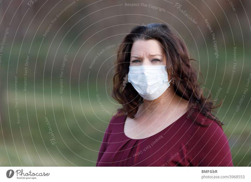 Frau trägt Mundschutz im Freien Pandemie Corona Virus Schutz Vorschriften Gesundheit schützen Ansteckung vermeiden verstecken wd Corona-Virus Infektionsgefahr