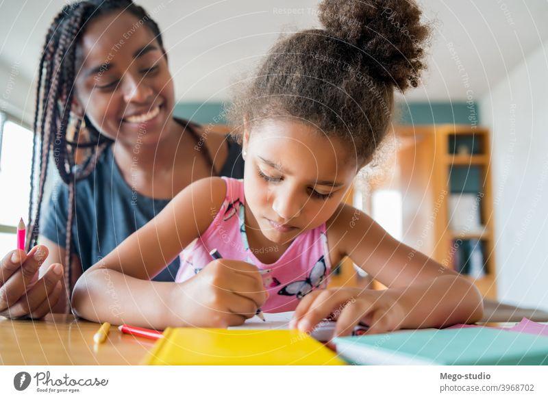 Ein Vater hilft seiner Tochter bei der Hausaufgabenbetreuung. Mutter Heimschule Schüler Lernen Lifestyle Quarantäne Familie Kinder Menschen absperren