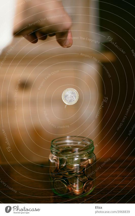 Eine Hand wirft einen Euro in ein Gefäß voller Münzen. Sparen. Geldmünzen sparen Vogelperspektive Glas Spardose Bargeld stoppen Kleinvieh kleine Änderung Holz