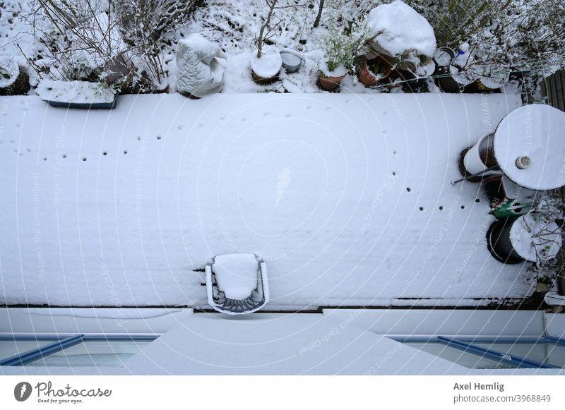 In der Nacht hat eine Katze im frischen Schnee die Terrasse erkundet und Spuren hinterlassen. Garten Winter Holzschutz spuren im schnee Abdrücke Wintergarten