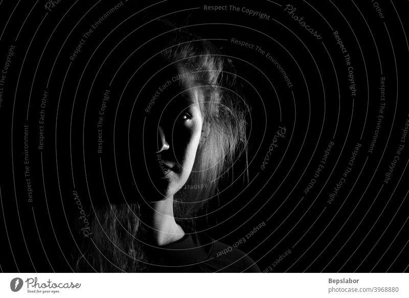 Schwarz-Weiß-Porträt einer jungen Frau auf schwarzem Hintergrund dramatisch Mädchen schön sinnlich dunkel beleuchtet obskur schwarz auf weiß trist Dunkelheit