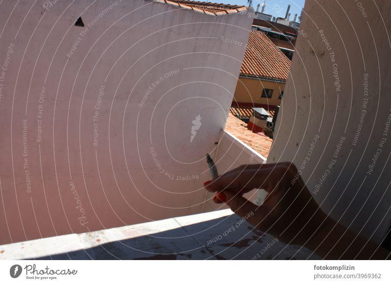 weibliche Hand mit Zigarette an einer Fensterbrüstung mit Blick auf Hinterhof rauchen Rauchen rauchend Tabak Brüstung Fensterblick Ausblick zuhause lockdown