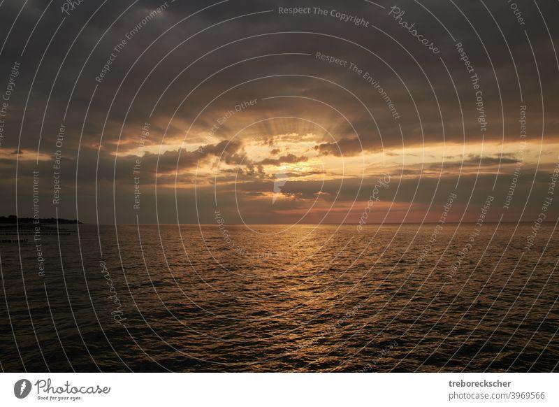 hellen und dramatischen Sonnenuntergang mit vielen Farben und einem bewölkten Himmel über dem Meer der Ostsee Natur MEER Sonnenaufgang orange Horizont