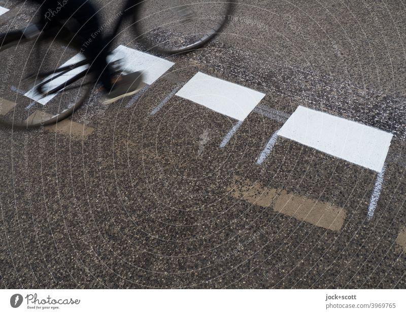 Radfahrer fährt über die frisch aufgemalte Straßenmakierung Fahrbahnmarkierung Verkehrswege Asphalt Verkehrszeichen neu Verkehrsleitkegel Strichellinie