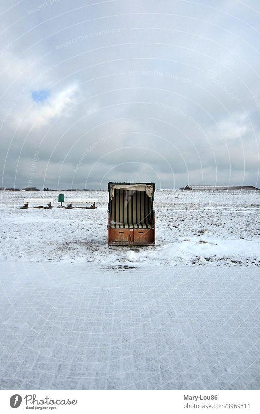 Einzelner Strandkorb im Schnee vor wolkenverhangenem Himmel Meer Insel Menschenleer Textfreiraum oben Textfreiraum unten Textfreiraum links Textfreiraum rechts