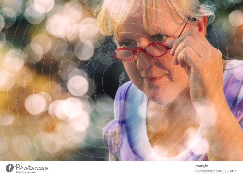AST10  l Eine sympathische Frau schaut über ihre Brille, hält sie fest und lächelt leicht. Sie ist umrahmt mit vielen Lens -Lichtern Lächeln freundlich