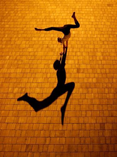 Turnerin bei Nacht mit Schatten schatten Licht Strukturen & Formen Kontrast Außenaufnahme Turnen Farbfoto handstand spagat contorsion bewegung